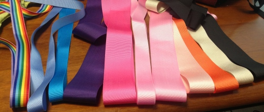 ribbons of varying thicknesses folded over in rainbow, blues, purple, pinks, orange, cream and black